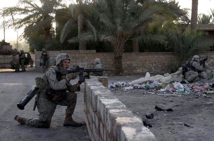 Lance Cpl. Jeffery Wilson, 3rd Platoon, Company K, 3rd Battalion, 1st Marine Regiment and Iraqi Security forces take cover on the streets in Haditha