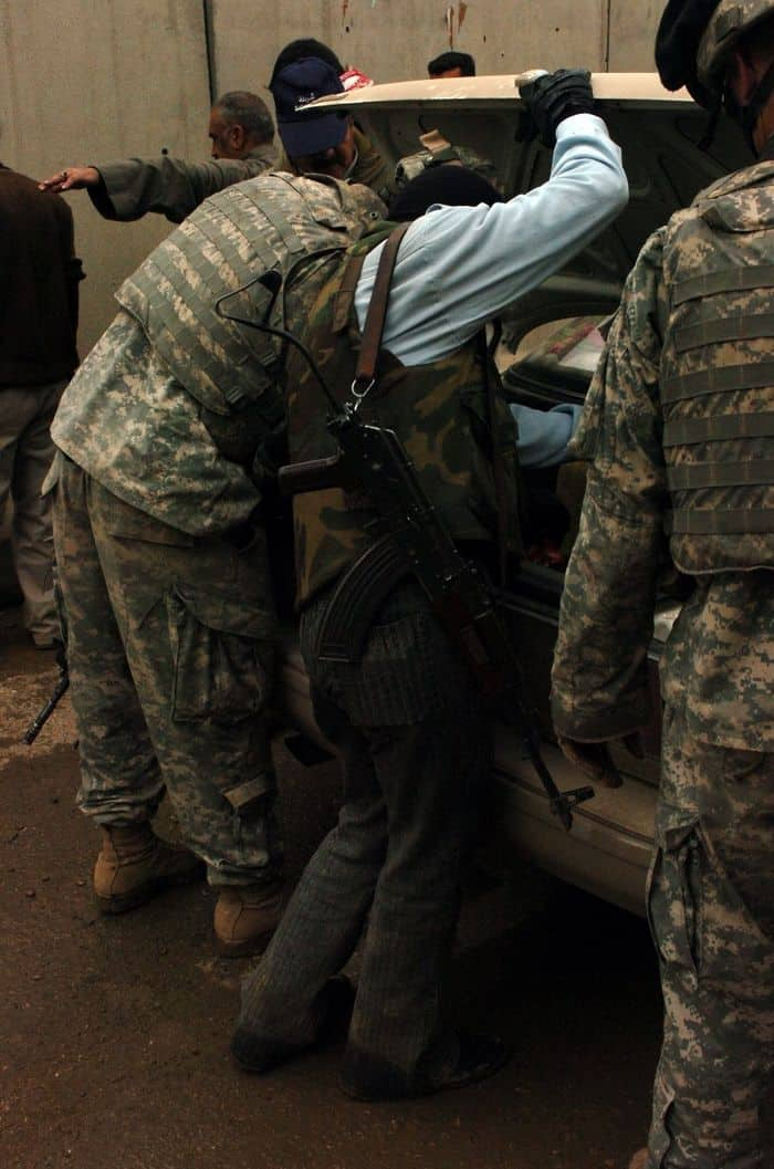 US Soldiers, Iraqi Police check a car at their checkpoint.