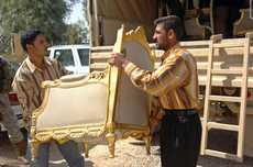 Iraqi workers move furniture that was given back to the Iraqi government.