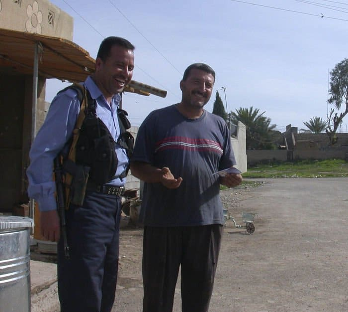 A Taza based Iraqi Police officer talks with a local merchant