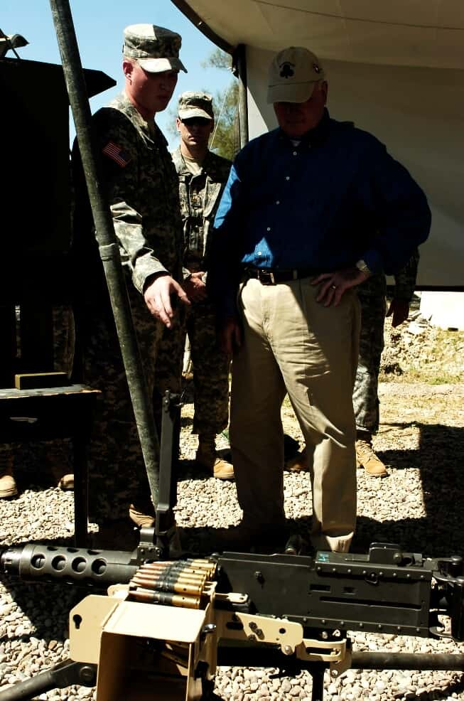 Sgt. Andrew S. Chard explains how his link deflector innovation works to the Secretary of the Army Francis Harvey
