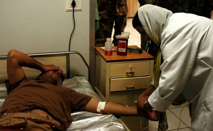 Suhad gives an IV to a heat injury patient