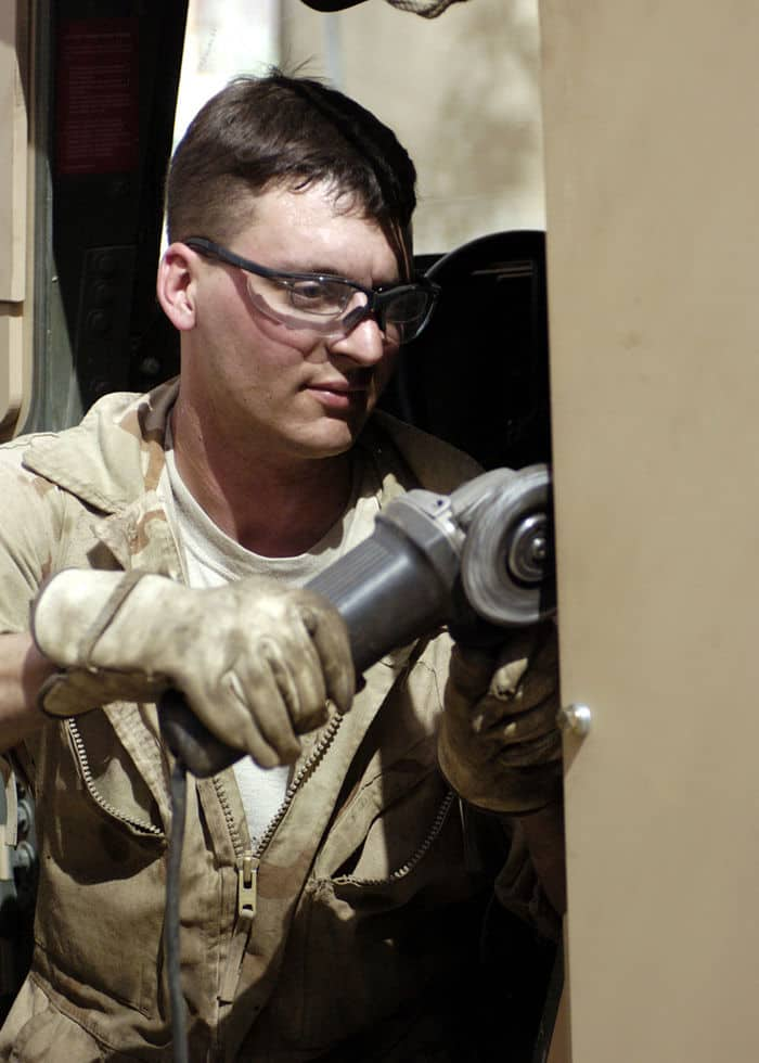Sergeant Ben Smith, a mechanic, grinds down the armor plated door of a humvee