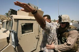 Lance Cpl. William A. Staley searches an Iraqi civilian at vehicle check point