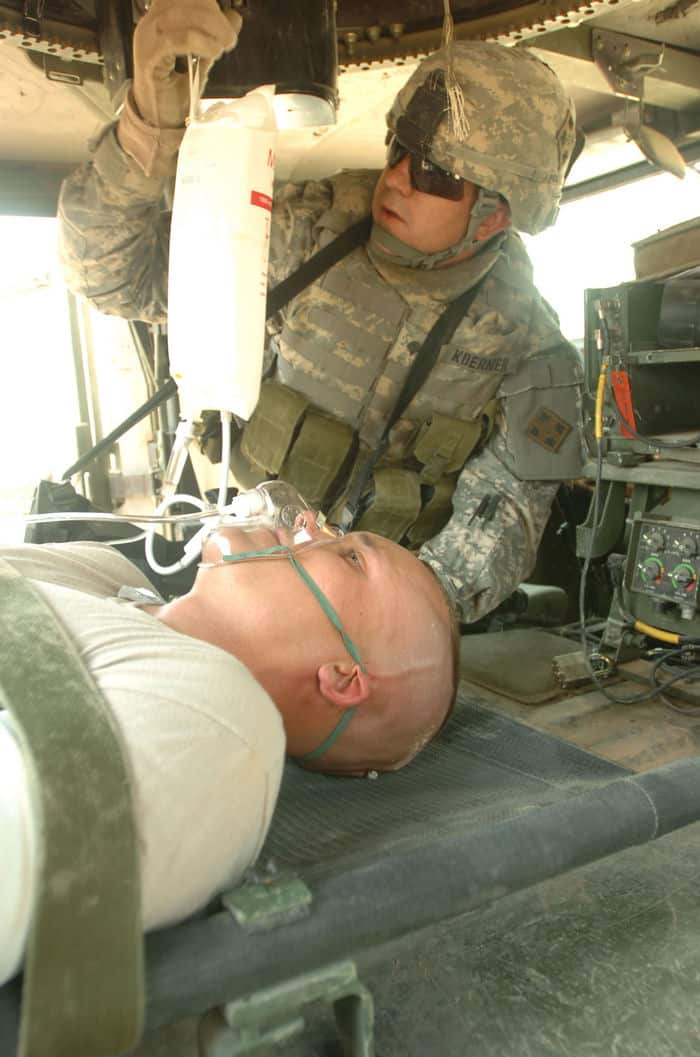 Spc. Brian Koerner applies an IV to a mock patient during medical training