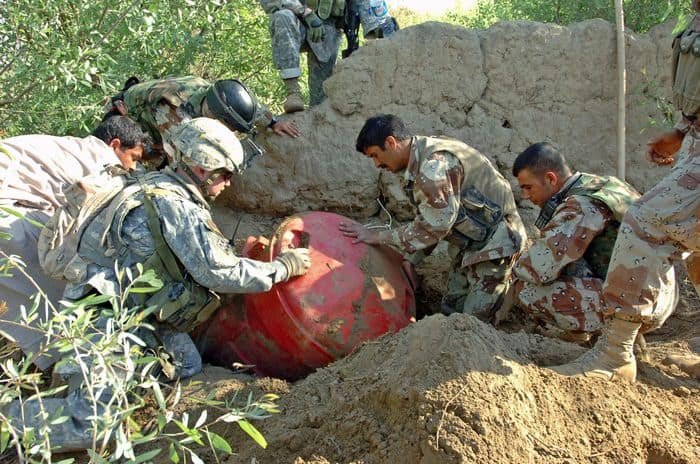 Soldiers from Company A, 1 8 Combined Arms Battalion, and Iraqi army uncover a barrel buried in an orchard on Jabouri Peninsula