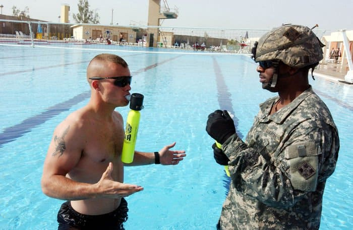 Sgt. Justin Folts, shows Staff Sgt. Derrick Gwin how to breathe using an oxygen tank