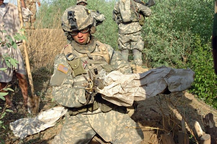 Spc. Dustyn Mitchell uncovers a rocket buried in an orchard on Jabouri Peninsula