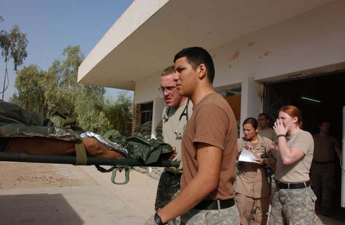 Pvt. Eleazar Garcia helps load an injured Iraqi Soldier into an ambulance