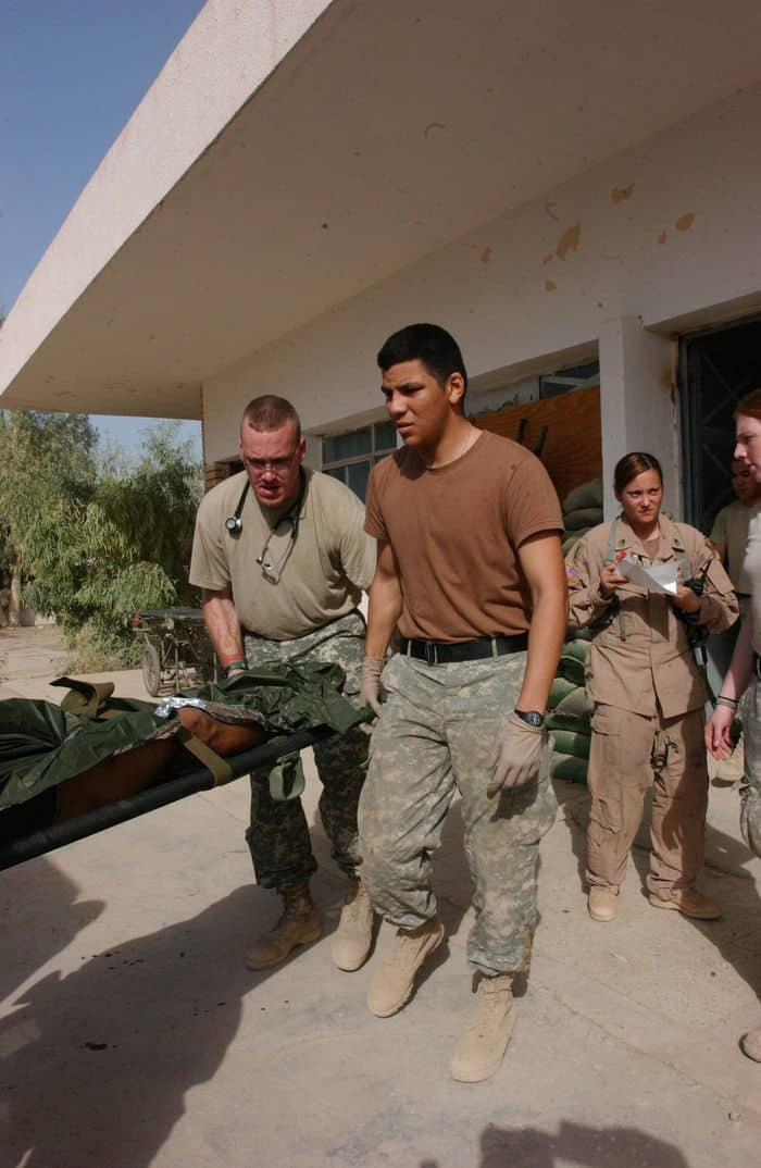combat medic Pvt. Eleazar Garciahelps carry an injured Iraqi Soldier on a litter
