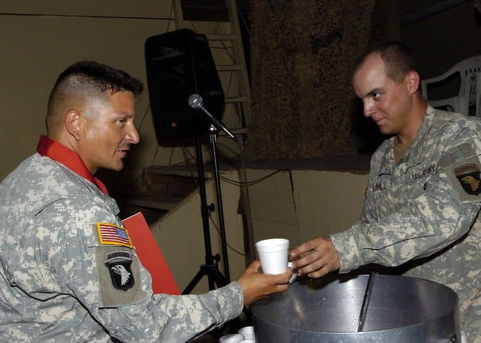 A Soldier with 2Bn, 320th Field Artillery Regiment, 1BCT, 101st Airborne takes a cup of Artillery punch, one of the rites of passage into the Honorable Order of St. Barbara