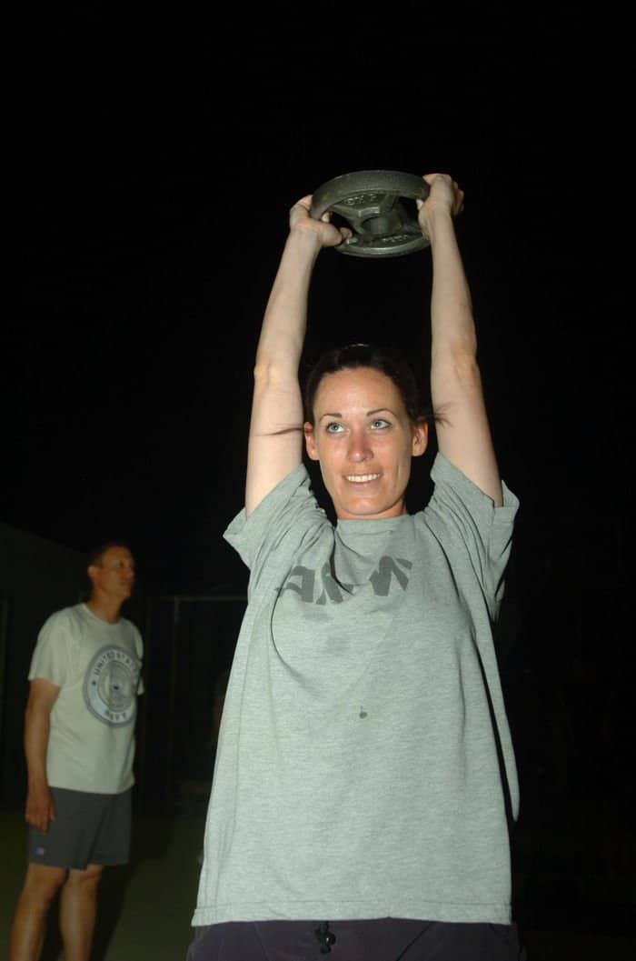 Staff Sgt. Ashley Campbell lifts a weight over her head while performing on a circuit