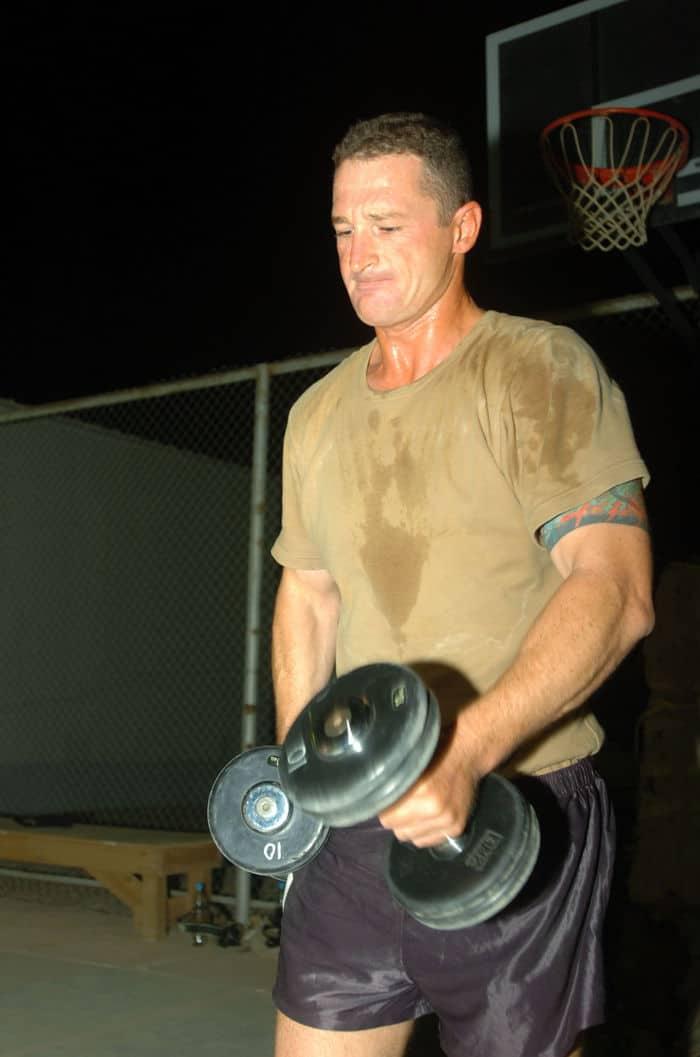 Australian Army Warrant Officer 2 Barry Conroy curls a weight