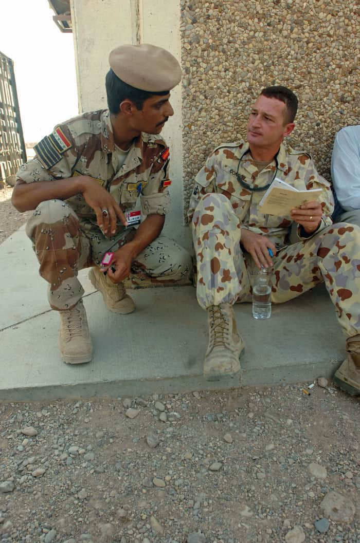 Australian Army Warrant Officer 2 Barry Conroy talks training issues with Iraqi Army Chief Sgt. Maj. Monsour at Kirkush Military Training Base