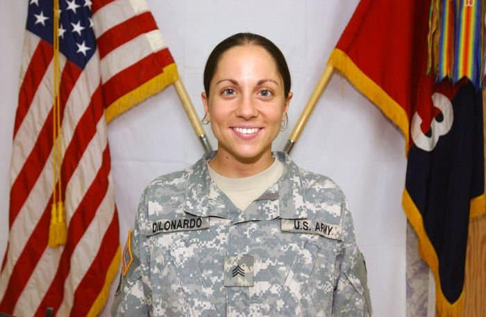 Sgt. Beth DiLonardo, native of Bricktown, N.J., intelligence analyst, in front of the U.S. flag and the Iron Brigade Colors