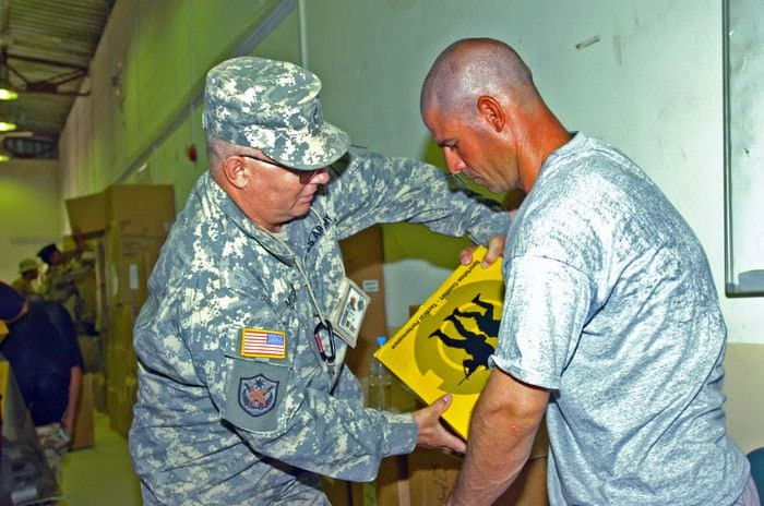 Iraqi Soldier gets help at KMTB Central Issue Facility with his new boots and uniforms from Sgt. 1st Class Donald Musser