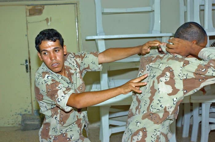New Iraqi Soldiers practice restraint techniques during their classroom training