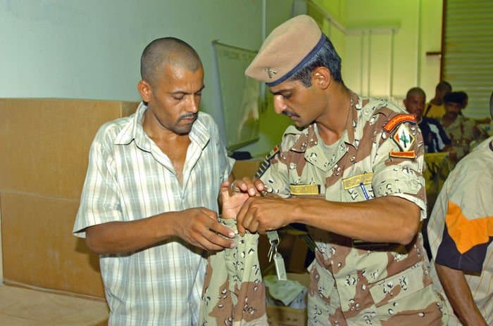 An Iraqi Soldier gets some help at KMTB Central Issue Facility with his new uniforms from Sgt. Maj. Monsour