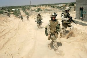 Marines of Weapons Company, 3rd Battalion, 2nd Marine Regiment trudge up a sandy hill after a patrol through a neighborhood east of Husayba, Iraq
