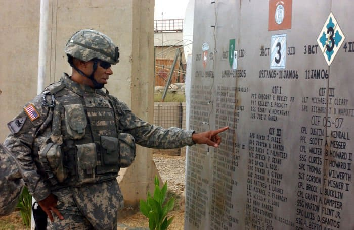 Brig. Gen. Dana Pittard, commander, Iraq Assistance Group, runs his fingers over the names of Soldiers who gave their lives in support of Operation Iraqi Freedom at FOB Warhorse near Baqubah, Iraq.