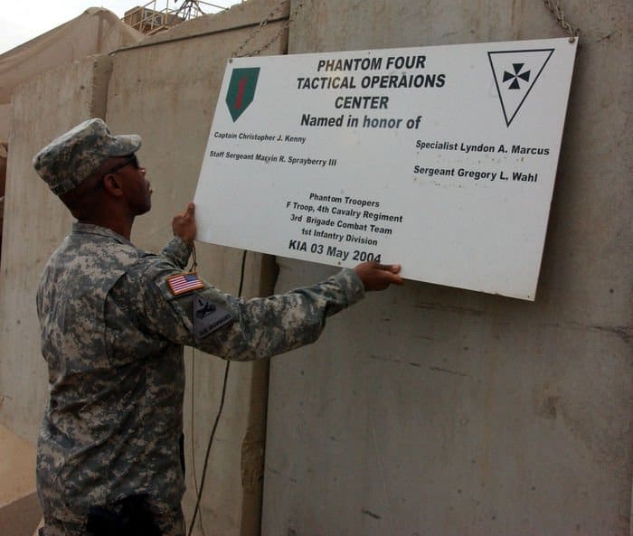 Brig. Gen. Dana Pittard, commander, Iraq Assistance Group, straightens a sign that bears the names of four Soldiers from 3rd Brigade, 1st Infantry Division who gave their lives in support of Operation Iraqi Freedom at the tactical operations center in FOB Warhorse near Baqubah, Iraq.