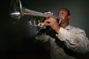 Sgt. Tarrell D. Jiles plays Taps in honor of Sgt. Jonathan J. Simpson during a memorial service at Camp Fallujah Chapel of Hope