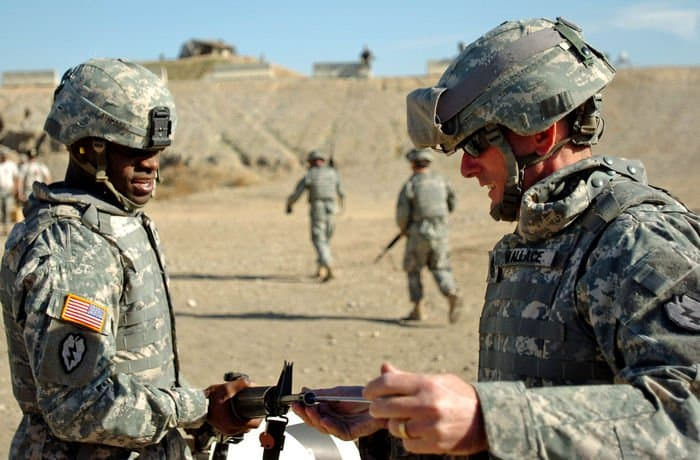 1st Sgt. Frank Wallace, HHT, 2 6th Cav. Regiment, clears Staff Sgt. Stewart Renaco, HHT, 2 6th Cav. Reg. weapon off the qualifying range.