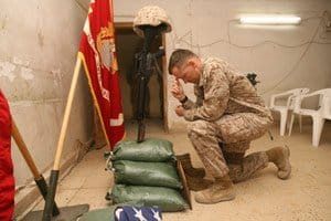 Lt. Col. Harold Van Opdorp, CO, kneels at the memorial to Lance Cpl. Brent E. Beeler