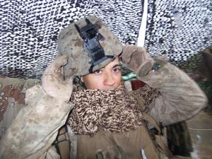 Lance Cpl. Daniel A. Ponce readies himself for post with a knitted scarf above Patrol Base 600, Iraq