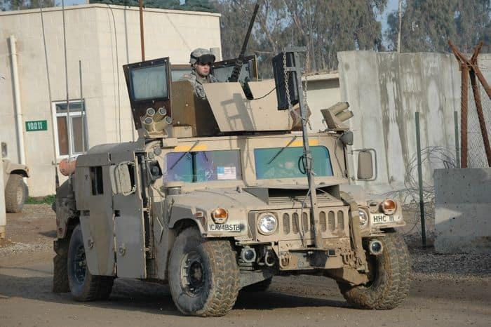 Spc. Brice Bell, military police officer mans the .50 caliber machine gun atop his uparmored humvee
