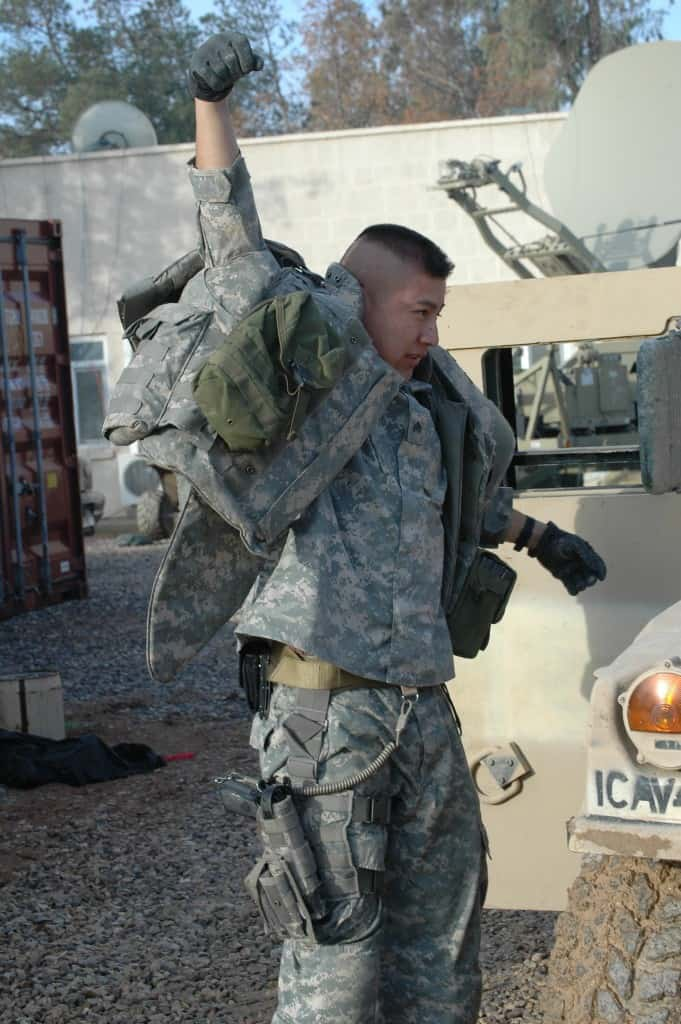Sgt. Raymund Begaye, military police team leader, puts on his outer tactical vest before heading out on a security escort mission