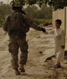 A Soldier from Company B, 5th Battalion, 20th Infantry Regiment, shakes hands with a boy in Baquba, Iraq.