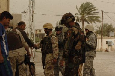 Lt. Col. Khalil Alohidi, commander of 4th Battalion, 2nd Brigade, 5th Iraqi Army Division, shakes hands with residents of Baquba, Iraq.