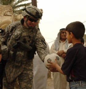 Maj. Kevin Luke of 4/2/5 Military Transition Team hands a soccer ball to a boy in Baquba, Iraq.