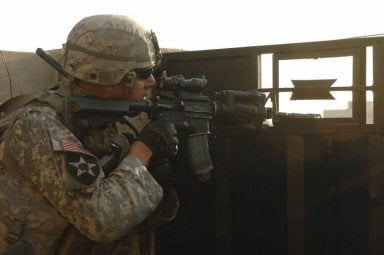 Sgt. 1st Class Joseph Labrosse, a platoon sergeant, scans rooftops in Baqouba, Iraq, for insurgent activity.