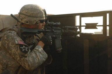 Sgt. 1st Class Joseph Labrosse, a platoon sergeant, scans rooftops in Baqouba, Iraq, for insurgent activity.