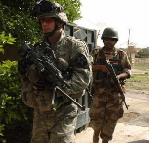 Spc. Edwin Kane of Company B, 5th Battalion, 20th Infantry Regiment, and a soldier from 2nd Brigade, 5th Iraqi Army Division, move through a gate in Baquba, Iraq.