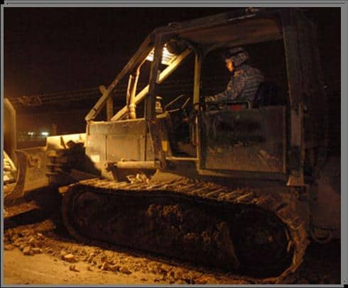 A Soldier excavates a site during the late evening hours.