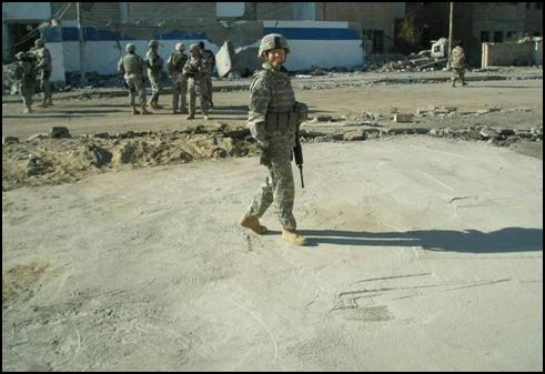 Company commander, Capt. Mara Boggs, walks across the newly repaired surface, which had been previously a large crater left after a vehicle borne improvised explosive device detonated in Mosul, Iraq.
