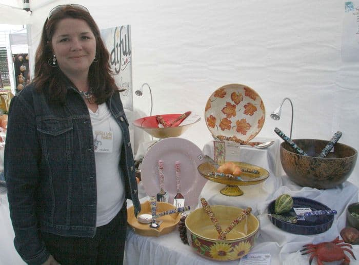 A pottery artist stands with her flying things.