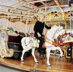 Jane Walentas, restorer of the carousel, on one of its wooden horses.