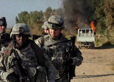 Spc. Billy Cassis, Sgt. Brandon Dean and other Soldiers, walk away from vehicle they torched near an insurgent safehouse south of Hussein Hamadi village, Diyala Province, Iraq.