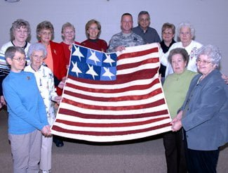 Members of the Quilts of Valor Foundation hold up a quilt made for Sgt. Tony Maddox, an Iraq war veteran injured by an IED.