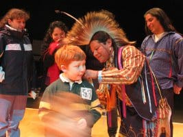 Carlos Ponce Eagle Feathers played by Maya and a young audience member at Thunderbird American Indian Dancers Annual Dance Concert and Pow Wow at Theater for the New City.