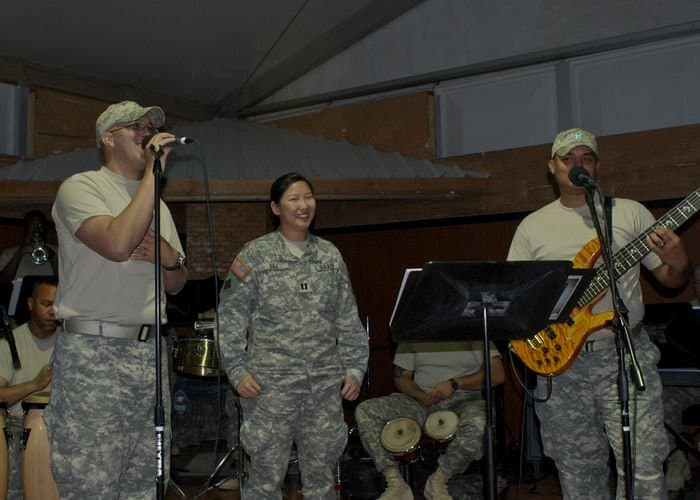 Spc. Danny Gonzalez and Sgt. Luis Feliciano of the Ritmo Latino ensemble and natives of Puerto Rico, sing to Capt. Becky Siu.