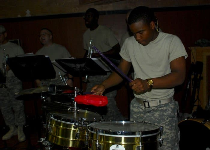 Spc. Ellington Zimmerman, of Dothan, Ala., performs a solo in the timbales drums during the performance of the Ritmo Latino ensemble