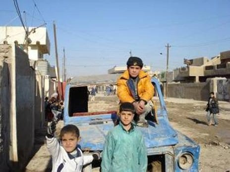 Children in the southeastern Baghdad neighborhood of Kamaliyah play while Coalition Soldiers talk to the Kamaliyah Sewer Project supervisor and 1st Battalion, 4th Brigade, 1st National Police Division commander.