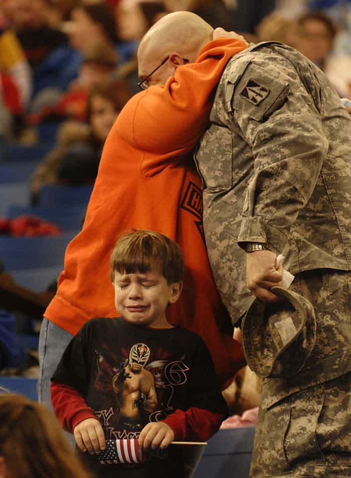 Sgt. Shane Pudgett hugs his wife goodbye as his son, Bryce, age 5, sheds a tear at the RCA Dome in Indianapolis.