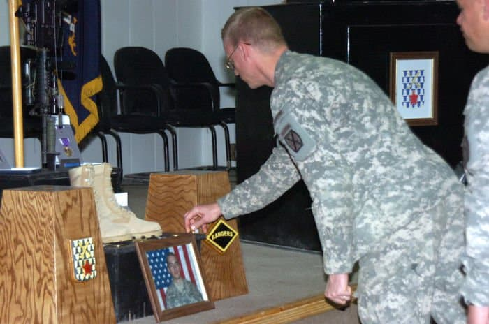 Lt. Col. Craig Collier, squadron commander presents a coin to pay his respects for the service and sacrifice of Spc. Duncan Charles Crookston.