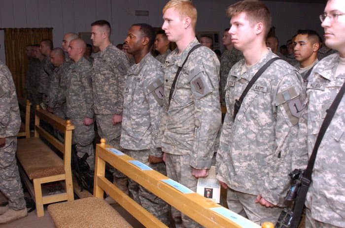 Soldiers stand at attention as they pay tribute to Spc. Duncan Charles Crookston in a memorial service.